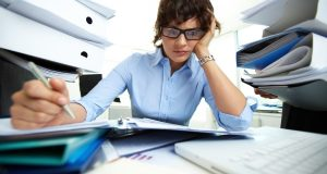Perplexed accountant doing financial reports being surrounded by huge piles of documents