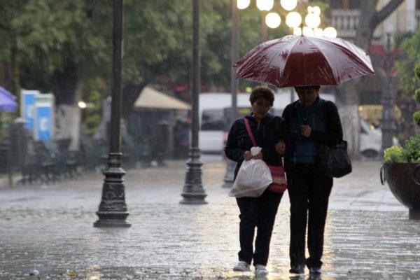 Pareja caminando bajo la lluvia en la CDMX