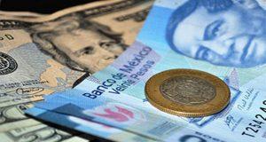 tipo de cambio: billete de dolar debajo de billete de 20 pesos y una moneda de diez