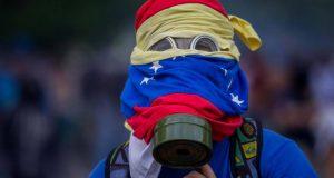 Activista venezolano cubierto su rostro con la bandera