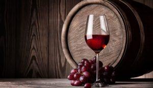 Copa de vino tinto en barrica con uvas