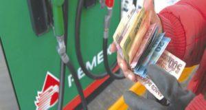 Bomba de gasolina con un despachador mostrando billetes
